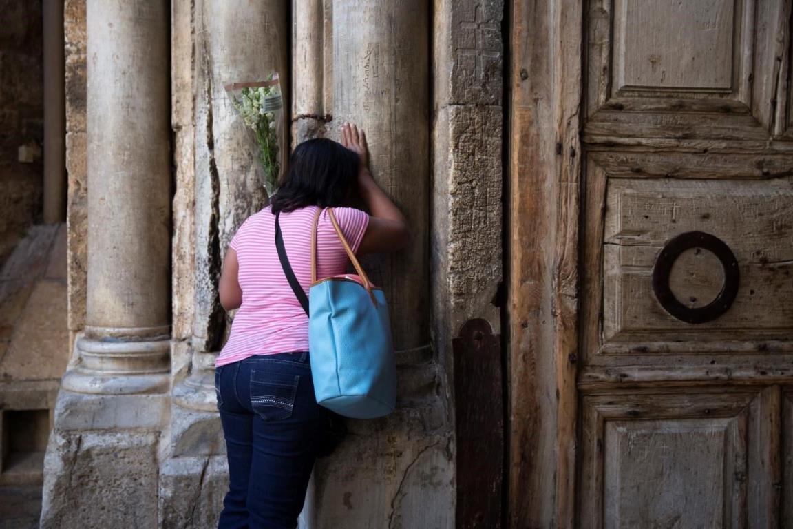 Женщина облокотилась на столб у входа в Храм Гроба Господня.