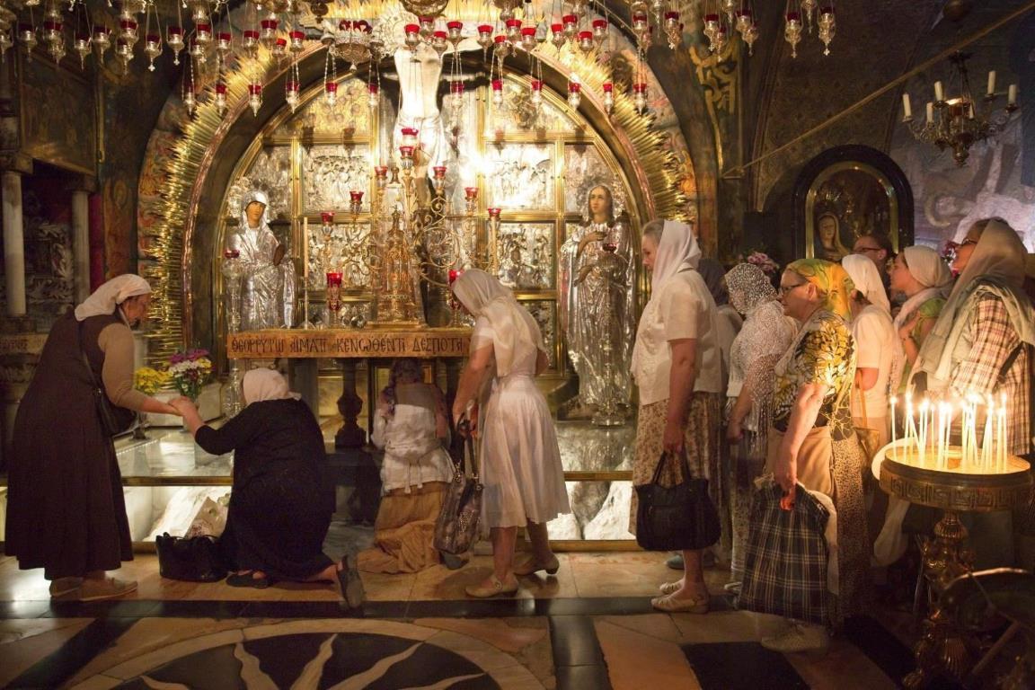 Православные паломники по очереди встают на колени, чтобы поцеловать то место, где был распят Иисус на 12-ой остановке Крестного пути.