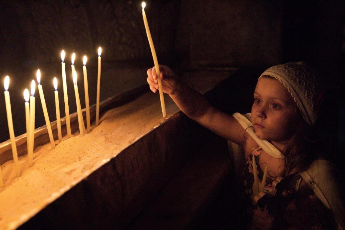 Маленькая девочка ставит свечу в Храме Гроба Господня.