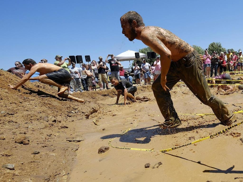 Во время одного из конкурсов бегуны выбираются из грязевой ямы.