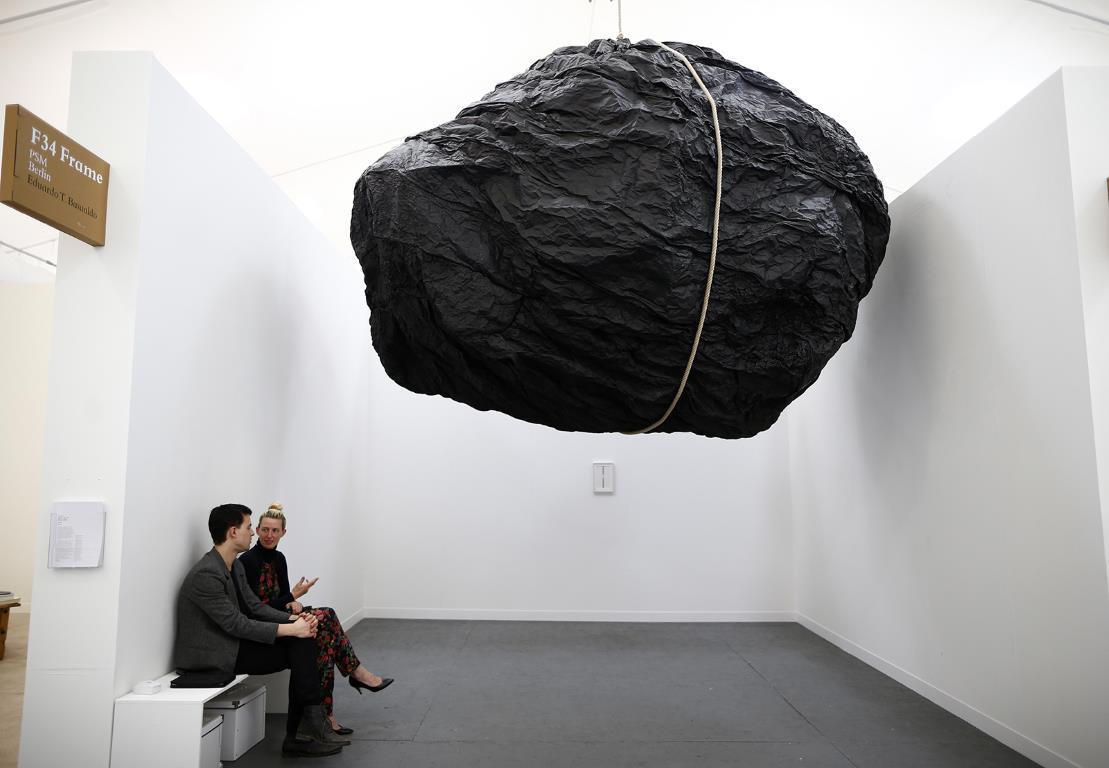 """Работники галереи сидят рядом со скульптурой """"Teoria"""" выставленной на """"Frieze Art Fair"""" в центре Лондона, автором которой является Эдуардо Басуальдо (Eduardo Basualdo)."""