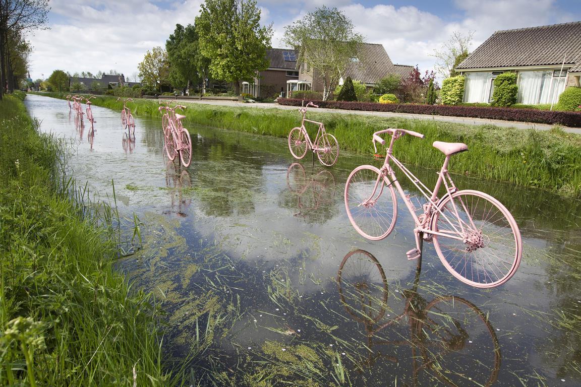 """Розовые велосипеды над водой празднуют прибытие велогонки """"Giro d'Italia"""" в Schalkwijk, небольшой городк за пределами Утрехт, Нидерланды."""
