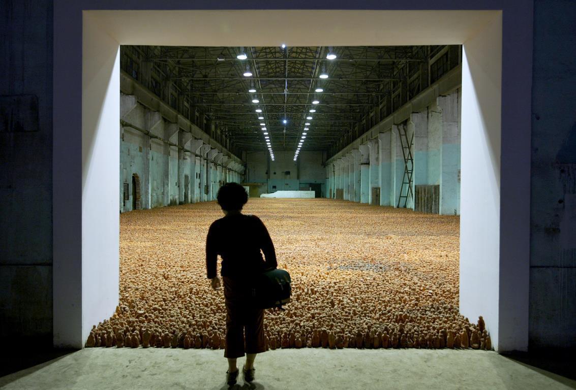 """Посетитель просматривает массивную скульптурную инсталляцию, заполняющую заводской склад на выставке британского художника Энтони Гормли (Antony Gormley) под названием """"Азиатское поле"""" (Asian Field) в Шанхае."""